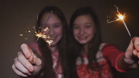 Δύο κορίτσια εφήβων που θέτουν και που χαμογελούν τα αναμμένα sparklers φιλμ μικρού μήκους