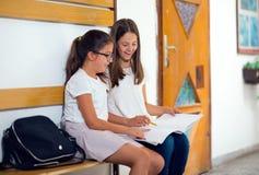 Δύο κορίτσια κάθονται στο σχολείο διαδρόμων Στοκ Φωτογραφία