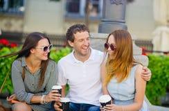 Δύο κορίτσια και ένας τύπος πίνουν τον καφέ και μιλούν ζωηρά στοκ εικόνα με δικαίωμα ελεύθερης χρήσης