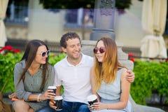 Δύο κορίτσια και ένας τύπος πίνουν τον καφέ και μιλούν ζωηρά στοκ εικόνες