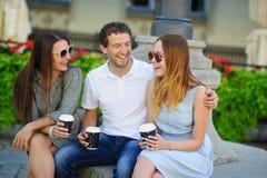 Δύο κορίτσια και ένας τύπος πίνουν τον καφέ και μιλούν ζωηρά στοκ φωτογραφία με δικαίωμα ελεύθερης χρήσης