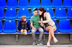 Δύο κορίτσια και ένα αγόρι κάθονται στις μπλε πολυθρόνες Στοκ Φωτογραφία