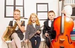 Δύο κορίτσια και αγόρι που παίζουν τα μουσικά όργανα Στοκ εικόνα με δικαίωμα ελεύθερης χρήσης