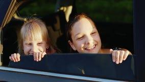 Δύο κορίτσια 6 και 11 διασκέδασης χρονών φαίνονται έξω το παράθυρο αυτοκινήτων Να εξισώσει πριν από το ηλιοβασίλεμα Έννοια - όπως φιλμ μικρού μήκους