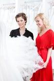 Δύο κορίτσια κοιτάζουν επίμονα στο φόρεμα στοκ εικόνες