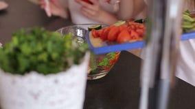 Δύο κορίτσια κόβουν τις ντομάτες και τα αγγούρια σε έναν ξύλινους πίνακα και έναν χορό, κινηματογράφηση σε πρώτο πλάνο απόθεμα βίντεο