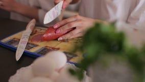 Δύο κορίτσια κόβουν το λουκάνικο σε έναν τέμνοντα πίνακα, που μαγειρεύει το πρόγευμα στην κουζίνα απόθεμα βίντεο