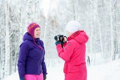 Δύο κορίτσια με μια κάμερα που παίρνει τις εικόνες στο χιόνι το χειμώνα Στοκ Φωτογραφία
