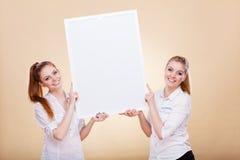 Δύο κορίτσια με την κενή παρουσίαση επιβιβάζονται Στοκ Φωτογραφία