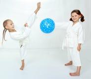 Δύο κορίτσια με την μπλε σφαίρα κτυπούν karate το λάκτισμα Στοκ Εικόνες