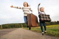 Δύο κορίτσια με τη βαλίτσα που στέκεται για το δρόμο στοκ εικόνα