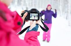 Δύο κορίτσια με τη κάμερα που παίρνει τις εικόνες στο χιόνι το χειμώνα Στοκ φωτογραφία με δικαίωμα ελεύθερης χρήσης