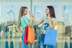 Δύο κορίτσια με τις ζωηρόχρωμες τσάντες αγορών πέντε υψηλά Εποχή πωλήσεων Στοκ Εικόνες