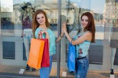 Δύο κορίτσια με τις ζωηρόχρωμες τσάντες αγορών πέντε υψηλά Εποχή πωλήσεων Στοκ Φωτογραφία