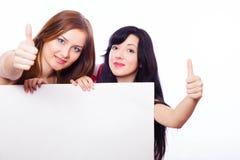 Δύο κορίτσια με το έμβλημα. Στοκ Εικόνες