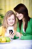 Δύο κορίτσια με το κινητό τηλέφωνο Στοκ Εικόνες