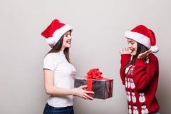 Δύο κορίτσια μοιράζονται το κιβώτιο δώρων Χριστουγέννων Στοκ Εικόνα