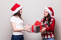 Δύο κορίτσια μοιράζονται το κιβώτιο δώρων Χριστουγέννων Στοκ Φωτογραφία