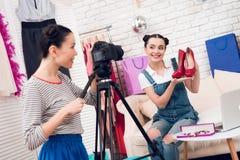Δύο κορίτσια μόδας blogger κρατούν ψηλά τα κόκκινα παπούτσια με ένα κορίτσι πίσω από τη κάμερα Στοκ εικόνα με δικαίωμα ελεύθερης χρήσης