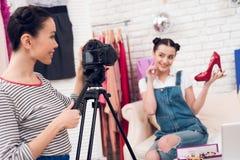 Δύο κορίτσια μόδας blogger κρατούν ψηλά τα κόκκινα παπούτσια με ένα κορίτσι πίσω από τη κάμερα Στοκ φωτογραφία με δικαίωμα ελεύθερης χρήσης