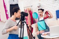Δύο κορίτσια μόδας blogger κρατούν ψηλά τα κόκκινα παπούτσια με ένα κορίτσι πίσω από τη κάμερα Στοκ Εικόνες