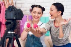 Δύο κορίτσια μόδας blogger κρατούν ψηλά τα κόκκινα σφουγγάρια στη κάμερα στοκ φωτογραφίες