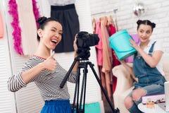Δύο κορίτσια μόδας blogger κρατούν ψηλά τη ζωηρόχρωμη τσάντα με ένα κορίτσι πίσω από τη κάμερα Στοκ Εικόνα