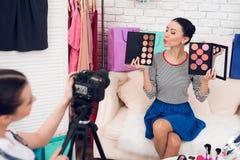 Δύο κορίτσια μόδας blogger κρατούν ψηλά τις ζωηρόχρωμες σκιές ματιών με ένα κορίτσι πίσω από τη κάμερα Στοκ φωτογραφία με δικαίωμα ελεύθερης χρήσης