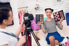Δύο κορίτσια μόδας blogger κρατούν ψηλά τις ζωηρόχρωμες σκιές ματιών με ένα κορίτσι πίσω από τη κάμερα Στοκ Εικόνες