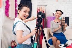 Δύο κορίτσια μόδας blogger κρατούν ψηλά τις ζωηρόχρωμες σκιές ματιών με ένα κορίτσι πίσω από τη κάμερα Στοκ εικόνα με δικαίωμα ελεύθερης χρήσης