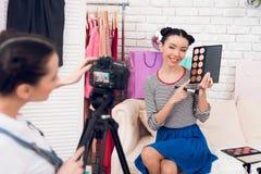 Δύο κορίτσια μόδας blogger κρατούν ψηλά τις ζωηρόχρωμες σκιές ματιών με ένα κορίτσι πίσω από τη κάμερα Στοκ Εικόνα