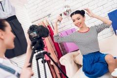 Δύο κορίτσια μόδας blogger κρατούν ψηλά τον ψεκασμό τρίχας με ένα κορίτσι πίσω από τη κάμερα Στοκ Φωτογραφία