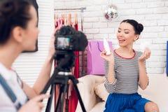 Δύο κορίτσια μόδας blogger κρατούν ψηλά το μπουκάλι με ένα κορίτσι πίσω από τη κάμερα Στοκ εικόνες με δικαίωμα ελεύθερης χρήσης
