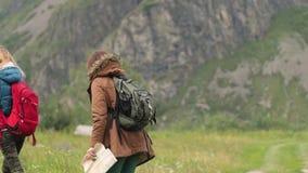 δύο κορίτσια οι ταξιδιώτες περπατούν κατά μήκος του δρόμου στα πλαίσια των βουνών Ταξιδιώτες φίλων με απόθεμα βίντεο