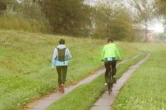 Δύο κορίτσια παίζουν τον αθλητισμό στον καιρό του ηλιόλουστου πρωινού Ποδηλασία και περπάτημα κάτω από τις πτώσεις βροχής στον ηλ στοκ εικόνες