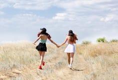 Δύο κορίτσια περπατούν γύρω από τα χέρια εκμετάλλευσης τομέων Καλή ηλιόλουστη ημέρα, τέλειος χρόνος στο περπάτημα Στοκ εικόνες με δικαίωμα ελεύθερης χρήσης