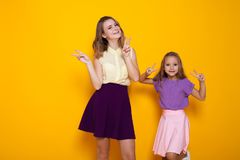 Δύο κορίτσια που έχουν τη διασκέδαση παρουσιάζουν δάχτυλα Στοκ Εικόνες
