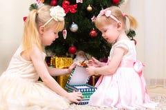 Δύο κορίτσια που ανοίγουν το δώρο Χριστουγέννων Στοκ εικόνα με δικαίωμα ελεύθερης χρήσης