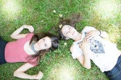 Δύο κορίτσια που βρίσκονται σε μια πράσινη χλόη στο λιβάδι λουλουδιών Στοκ φωτογραφία με δικαίωμα ελεύθερης χρήσης