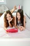 Δύο κορίτσια που βρίσκονται στο κρεβάτι και που εξετάζουν την ταμπλέτα κάθετος Στοκ εικόνες με δικαίωμα ελεύθερης χρήσης