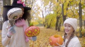 Δύο κορίτσια που γιορτάζουν αποκριές με το σκελετό, το φανάρι γρύλων ο ` και το καπέλο μαγισσών απόθεμα βίντεο