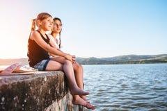 Δύο κορίτσια που εγκαθιστούν με τη θάλασσα και τη χαλάρωση Στοκ φωτογραφία με δικαίωμα ελεύθερης χρήσης