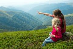 Δύο κορίτσια που εξετάζουν τα βουνά στοκ φωτογραφία