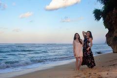 Δύο κορίτσια που θέτουν στην παραλία μπροστά από το βράχο Στοκ Φωτογραφία