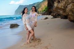 Δύο κορίτσια που θέτουν στην παραλία μπροστά από το βράχο Στοκ Φωτογραφίες