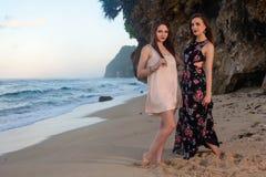 Δύο κορίτσια που θέτουν στην παραλία μπροστά από το βράχο Στοκ φωτογραφίες με δικαίωμα ελεύθερης χρήσης