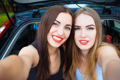 Δύο κορίτσια που θέτουν στο αυτοκίνητο Στοκ εικόνα με δικαίωμα ελεύθερης χρήσης