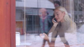 Δύο κορίτσια που κάθονται σε έναν καφέ με τα τηλέφωνα το χειμώνα απόθεμα βίντεο