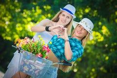 Δύο κορίτσια που κάνουν τη μορφή καρδιών με τα χέρια τους υπαίθρια Στοκ Εικόνες