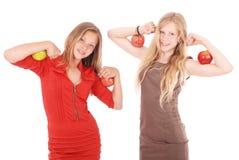 Δύο κορίτσια που κρατούν τα μήλα στους δικέφαλους μυς της στοκ εικόνες